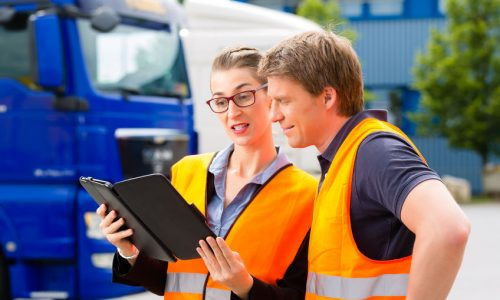 27288489 - logistics - proud driver or forwarder and female coworker with tablet computer, in front of trucks and trailers, on a transshipment point, its a good and successful team